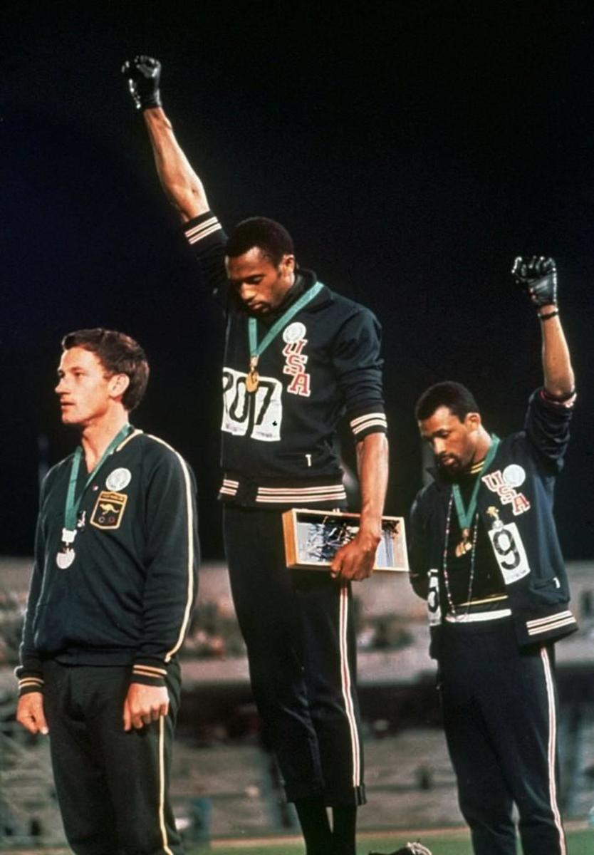 U.S. athletes Tommie Smith, center, and John Carlos raise gloved hands skyward during the playing of the Star Spangled Banner after Smith received the gold and Carlos the bronze for the 200 meter run at the Summer Olympic Games in Mexico City, 1968.