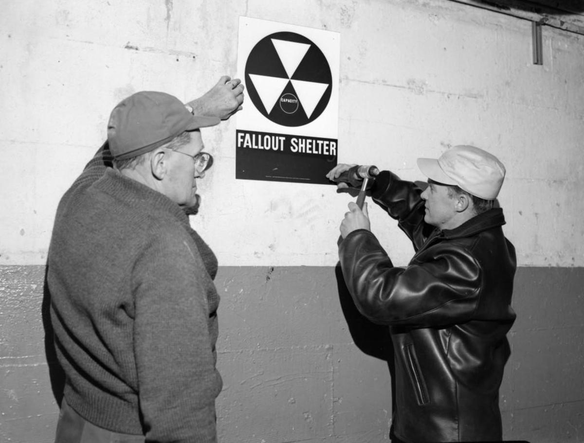 Men install fallout shelter sign in Chicago. (Credit: Kirn Vintage Stock/Corbis via Getty Images)