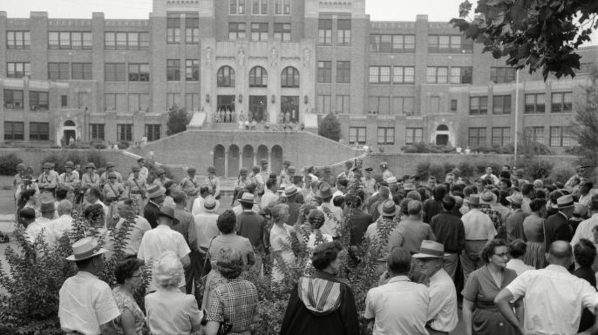 The crowd gathered outside Little Rock Central High School. The military  men were ordered by