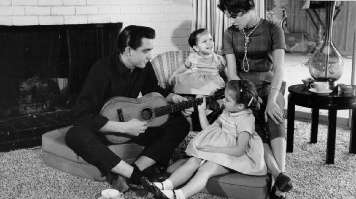 Country singer/songwriter Johnny Cash holds a guitar as his wife Vivian Liberto and daughters, Rosanne and Kathy, look on, 1957. (Credit: Michael Ochs Archives/Getty Images)