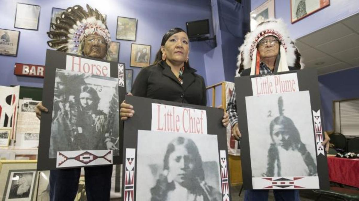 Yufna Soldier Wolf, center, of the Northern Arapaho, with tribal elders, Mark Soldier Wolf and Crawford White Sr., holds pictures of Little Plume, Horse and Little Chief. The three Arapaho children died about 135 years ago while attending a government-run school in Pennsylvania, the Carlisle Indian School, where they were buried.