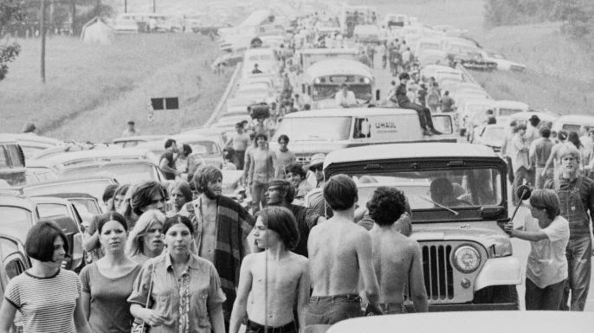 Crowds walk along roads choked with traffic on the way to Woodstock. (Credit: Hulton Archive/Getty Images)