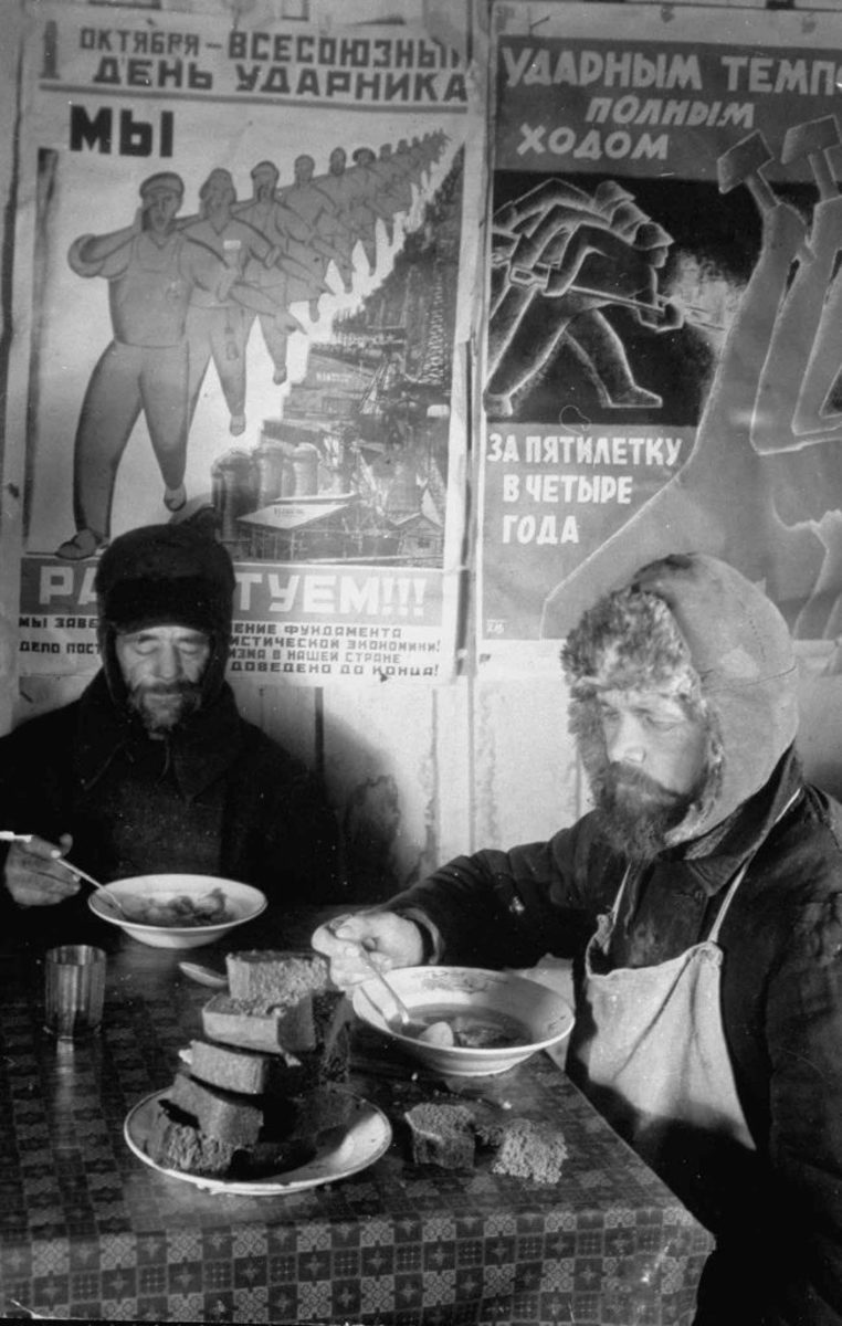 Two Russian workers eating bread and soup at a table in front of a wall covered with Soviet Communist Workers posters, 1931. (Credit: Margaret Bourke-White/The LIFE Picture Collection/Getty Images)