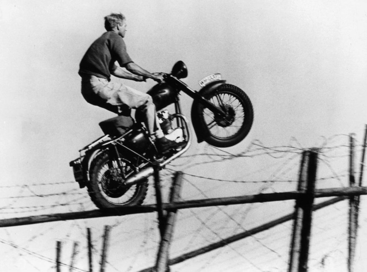 Steve McQueen's stunt double, Bud Ekin, flying through the sky on a motorcycle in a scene from the film The Great Escape, 1963. (Credit: United Artists/Getty Images)