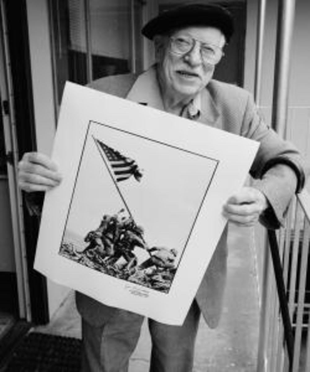 Photographer Joe Rosenthal poses with his Pulitzer Prize-winning photograph of U.S. Marines raising the flag on Mount Suribachi, Iwo Jima.  (Credit: David Hume Kennerly/Getty Images)