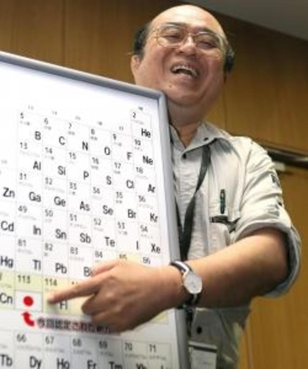 Kosuke Morita, who led the team at Riken institute that discovered the superheavy synthetic element, smiles as he points to a board displaying the new element 113.  (Credit: JIJI PRESS/AFP/Getty Images)
