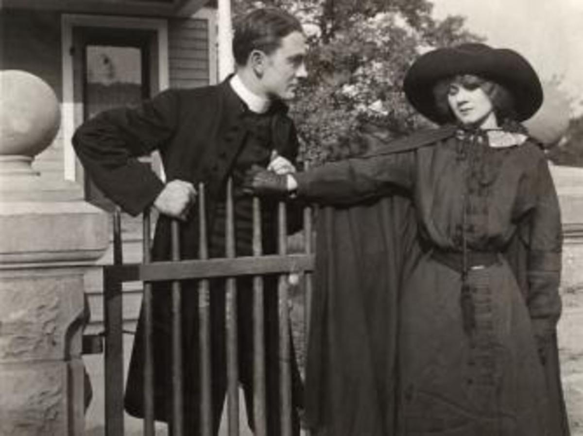 Owen Moore talks to Florence Lawrence in a scene still from a silent drama.