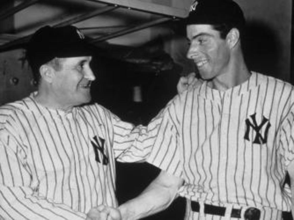 Yankees manager Joe McCarthy congratulates DiMaggio on tying Willie Keeler's record. (Credit: New York Times Co./Getty Images)