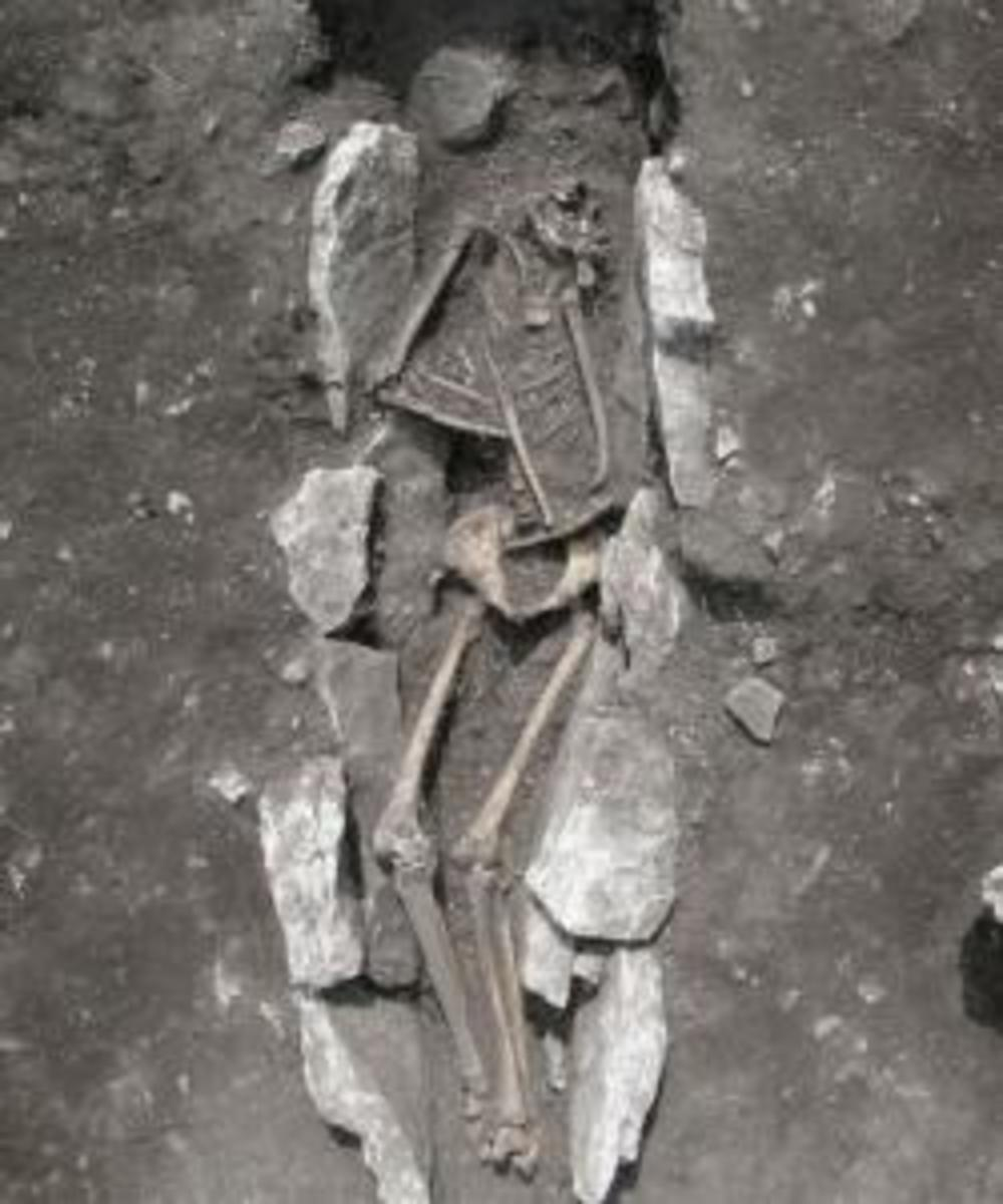 Human buried in the middle of the ash altar with covering plates in the pelvic area.