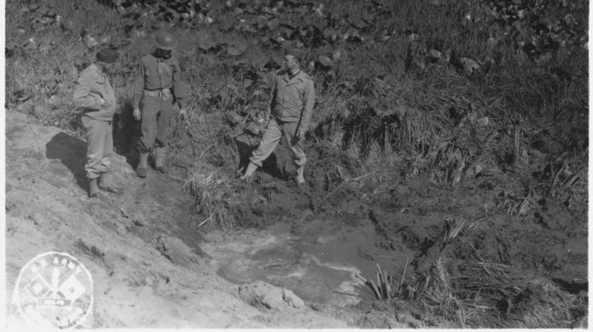 Soldiers inspect a crater caused by the Japanese attack at Fort Stevens.