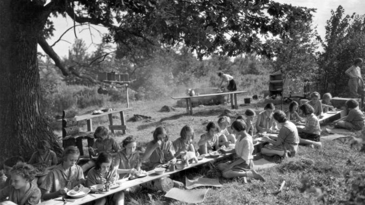The Junior Girl Scouts at Camp Merritt prepare their own lunches, and enjoy them too, East Hartland, Connecticut, mid 1920s. (Credit: Underwood Archives/Getty Images)
