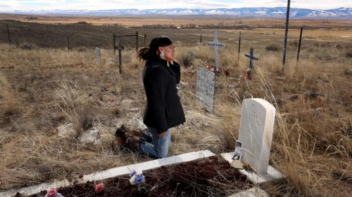 Yufna Soldier Wolf wipes away tears while kneeling at the grave of her great-grandfather, Chief Sharp Nose of the Northern Arapaho Tribe, at the family cemetery on the Wind River Reservation near Riverton, Wyoming.