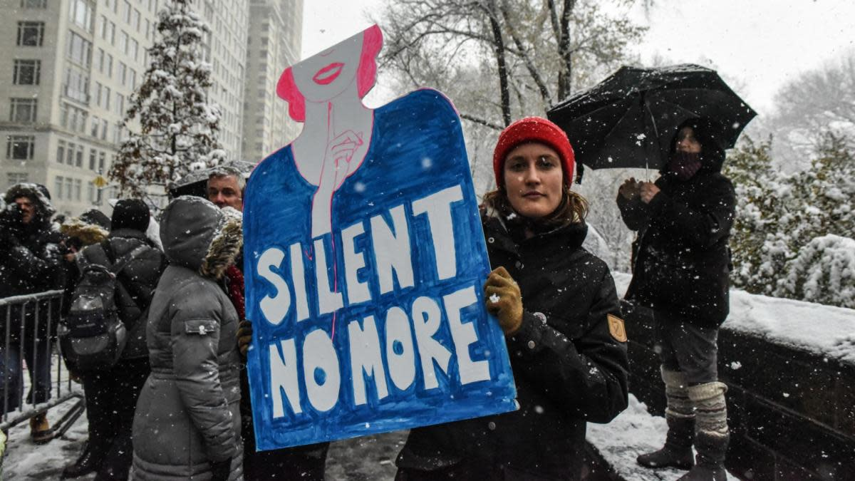 People carry signs addressing the issue of sexual harassment at a #MeToo rally in New York City, December 9, 2017. (Credit: Stephanie Keith/Getty Images)