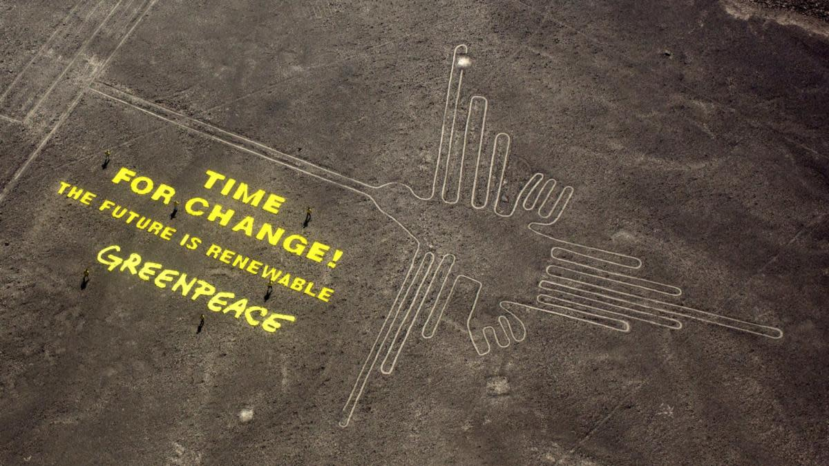 "Greenpeace activists standing next to large letters that spell out ""Time for Change: The Future is Renewable"" next to the hummingbird geoglyph in Nazca, Peru. (Credit:Rodrigo Abd/AP Photo)"