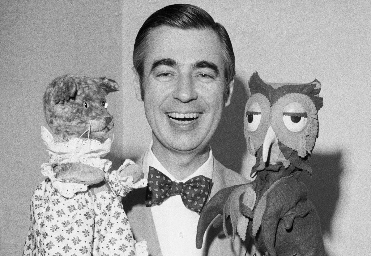"Fred Rogers of Mister Rogers' Neighborhood holds Henrietta Pussycat (left) and ""X"" the Owl during an interview. Rogers is an ordained Presbyterian minister and his ministry works to reach out to children and their families through mass media."