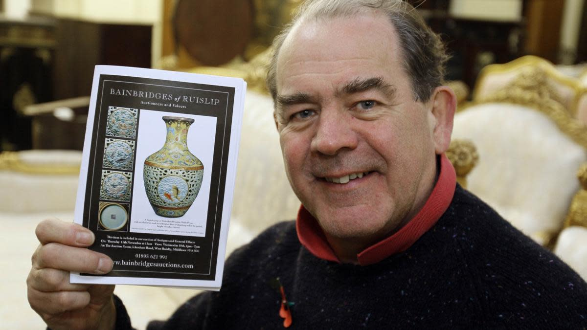 Auctioneer Peter Bainbridge holding the Bainbridges auction catalogue showing the 18th century Chinese porcelain vase that he auctioned in London, 2010. (Credit: Kirsty Wigglesworth/AP Photo)
