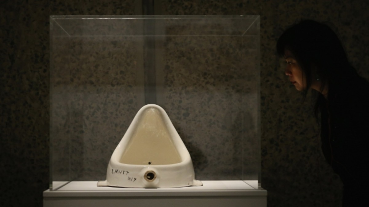 A woman looks at 'Fountain' by Marcel Duchamp during a press preview of an exhibition at the Barbican Art Gallery in London, England. (Credit: Dan Kitwood/Getty Images)