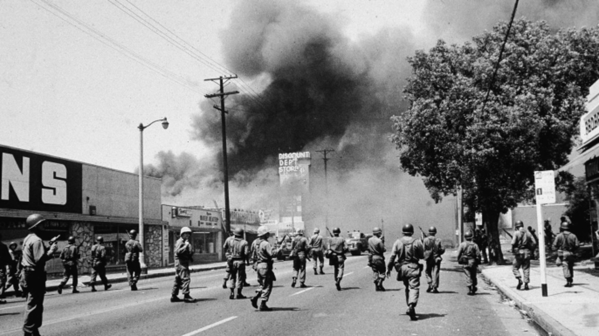 Armed National Guardsmen march toward smoke on the horizon during the street fires of the Watts riots, Los Angeles, California, 1965. (Credit: Hulton Archive/Getty Images)