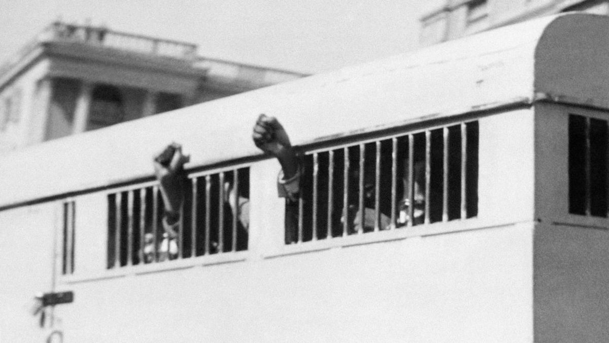 A group of men, among them anti-apartheid leader and ANC member Nelson Mandela, after being sentenced to life in prison with their fists still raised in defiance through the barred windows of the prison car.