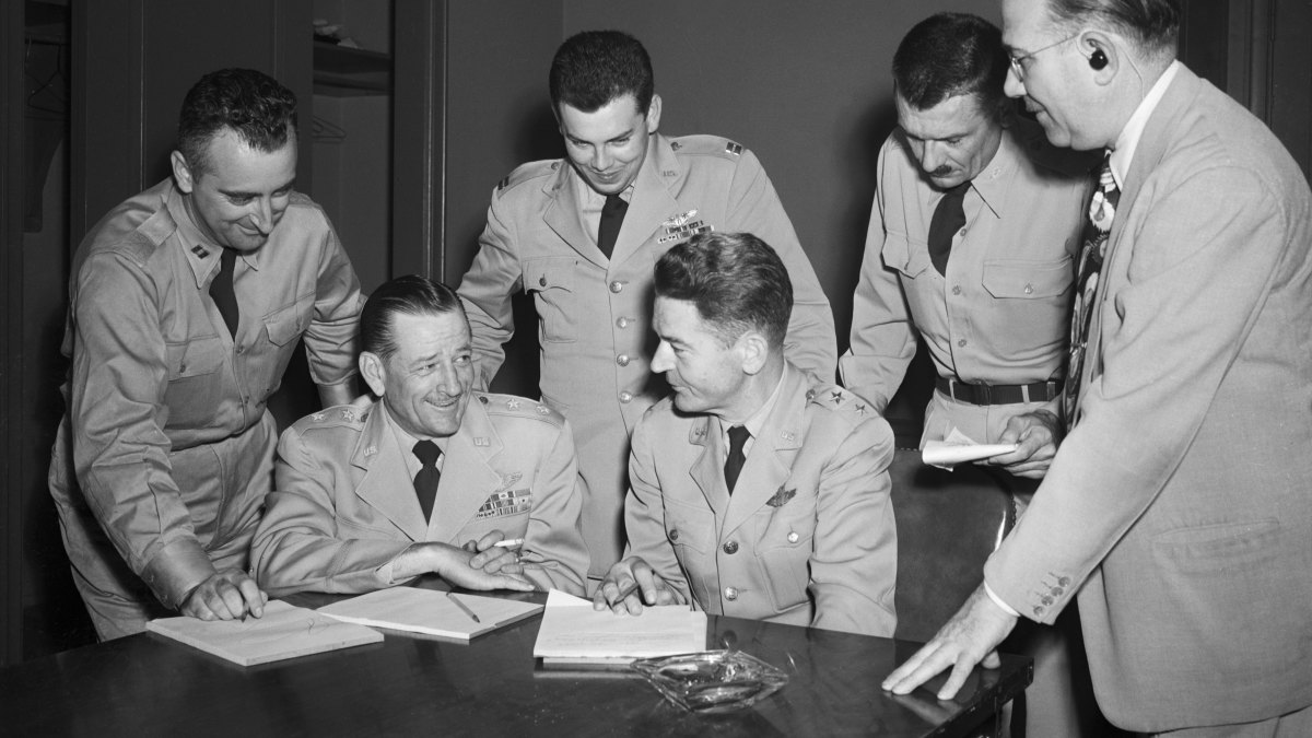 Captain Edward Ruppelt, standing between the two seated men, with other officers of the U.S. Air Force at a 1952 news conference where they announced the installment of more than 200 cameras in attempts to obtain data on the unidentified objects reported from various parts of the nation.