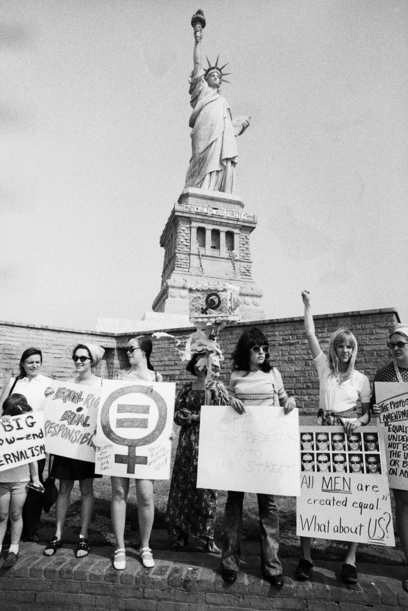 "A group of women rally at the Statue of Liberty in August, 1970. In the background on the Statue of Liberty reads a banner saying, ""Women of the World Unite."""