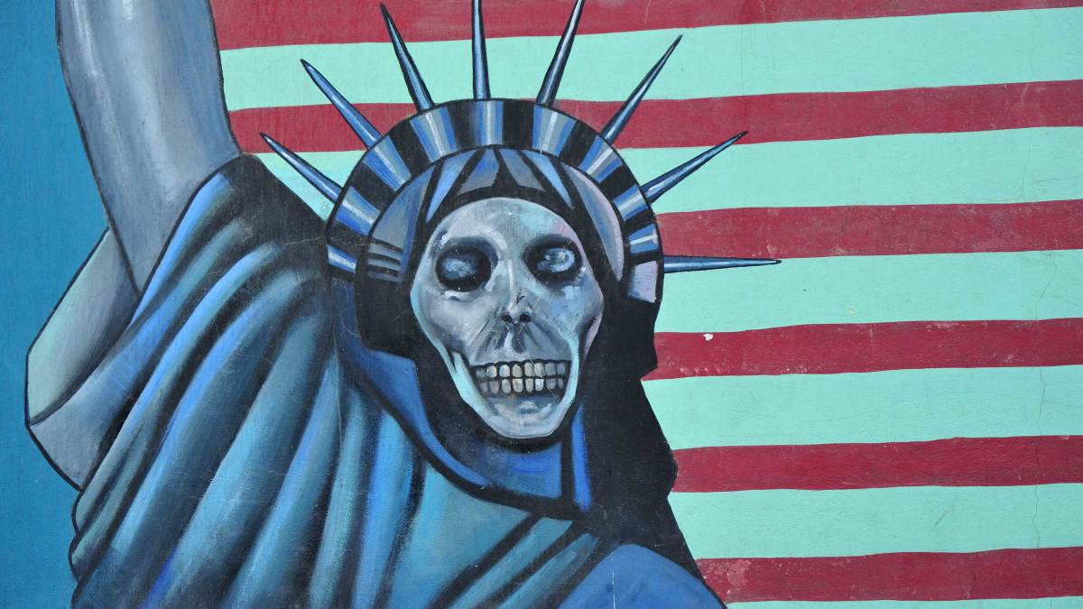 A mural of Statue of Liberty with a skull face in front of an American flag on the walls of the former US embassy in Tehran.