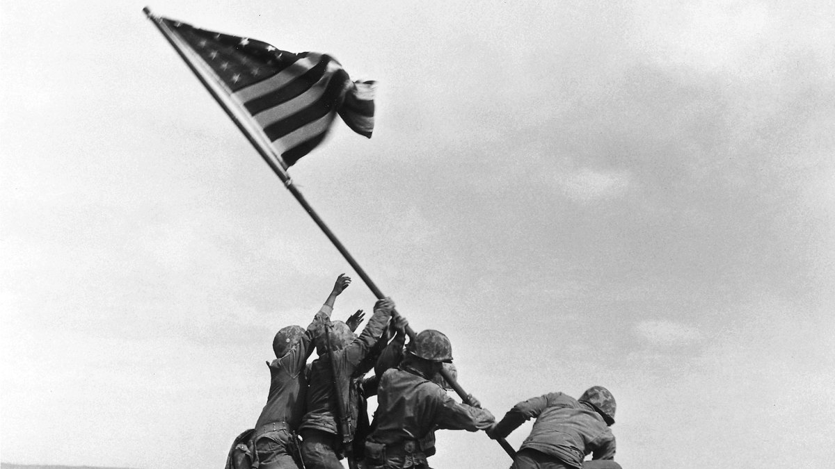 U.S. Marines of the 28th Regiment, 5th Division, raise the American flag atop Mt. Suribachi during the Battle of Iwo Jima, on February 23, 1945.