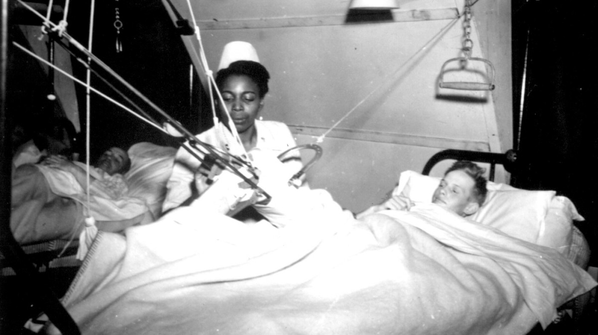 Lt. Florie E. Grant tending to a patient at a prisoner of war hospital, 1944