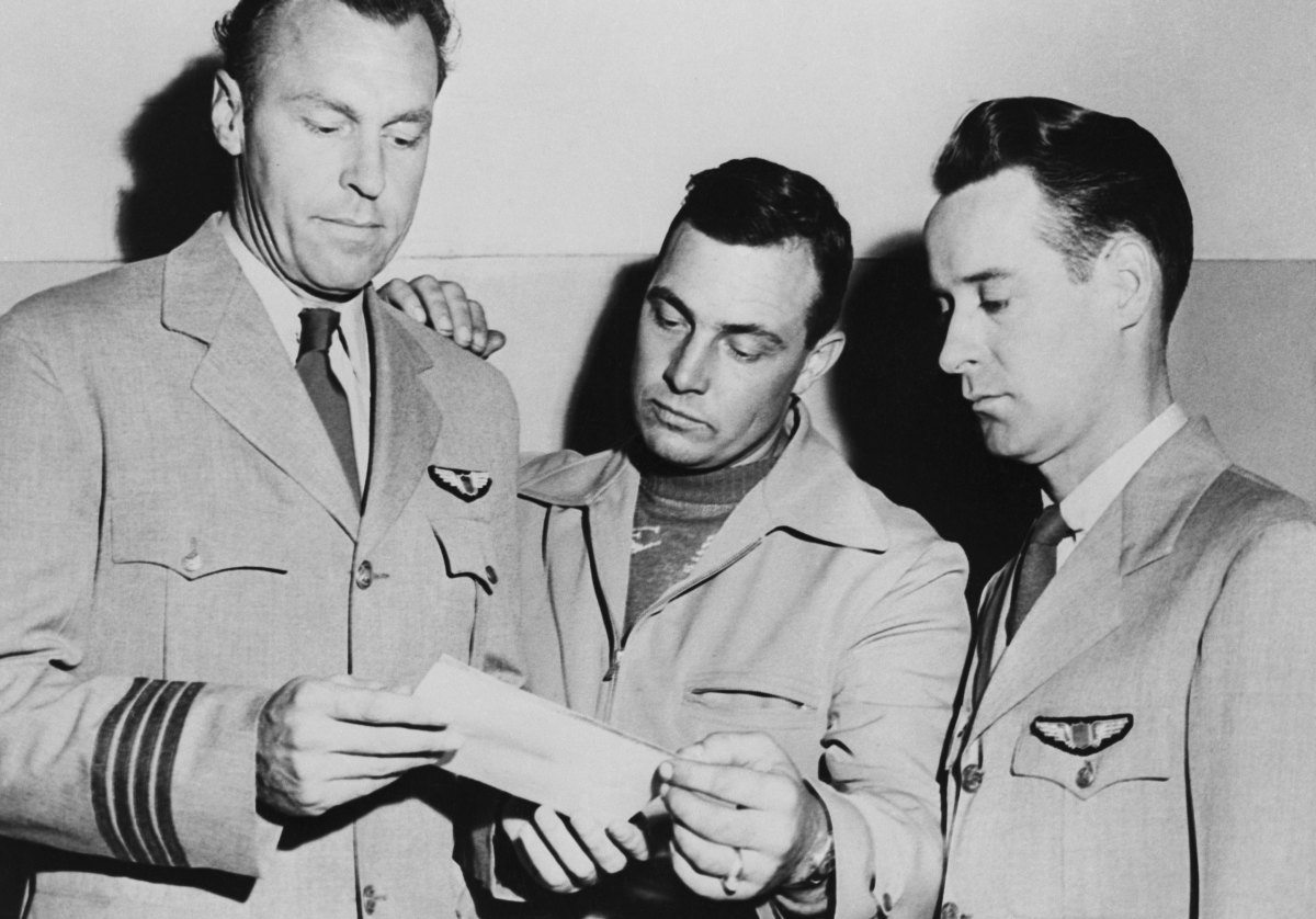 Kenneth Arnold, center, looks at a photo of an unidentified flying object they sighted while en route to Seattle, Washington with pilots E.J. Smith and Ralph E. Stevens.