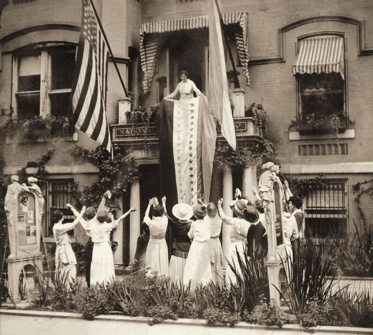American suffragist Alice Paul stands on a balcony at the National Women's Party headquarters and unfurls a banner in celebration of the state of Tennessee's ratification of the 19th Amendment, which guaranteed women the right to vote.