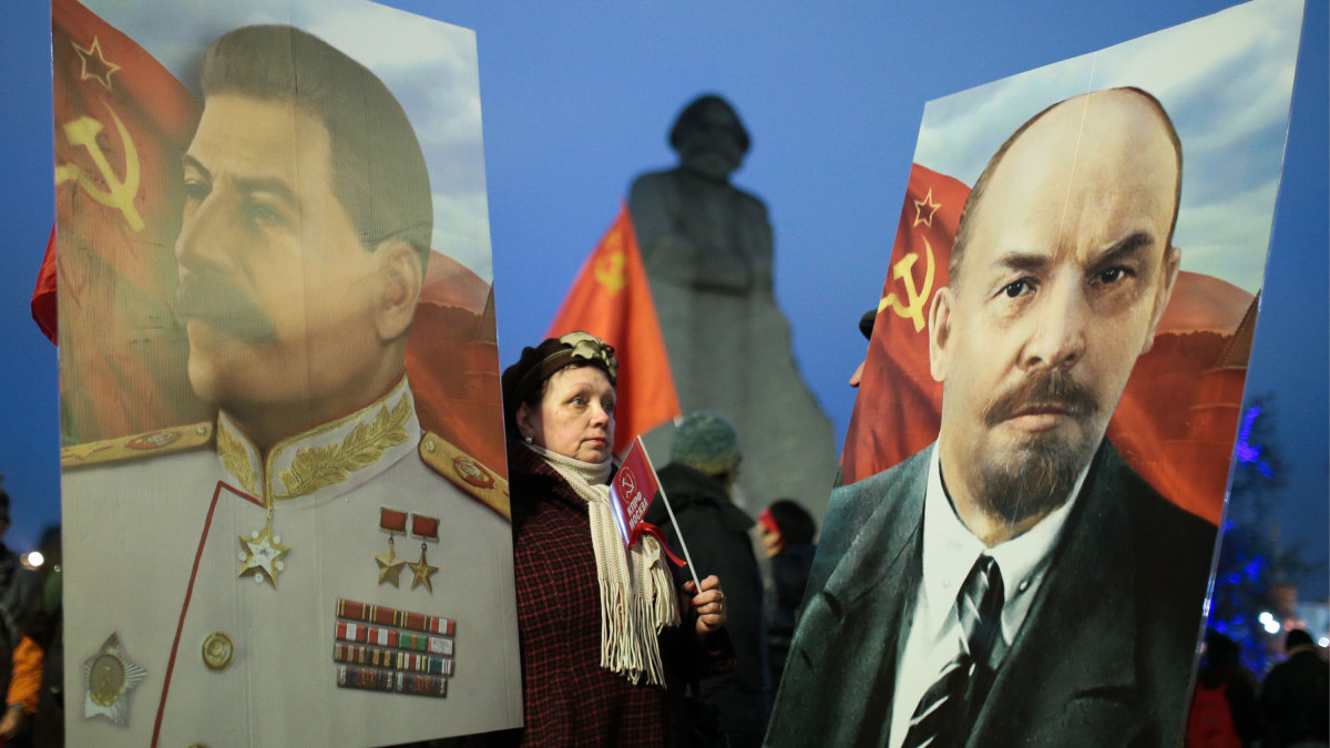 A woman is flanked by portraits of Soviet leader Joseph Stalin and Russian Revolutionary Vladimir Lenin as the Russian Communist Party rallies to mark the centenary of the 1917 Bolshevik Revolution.