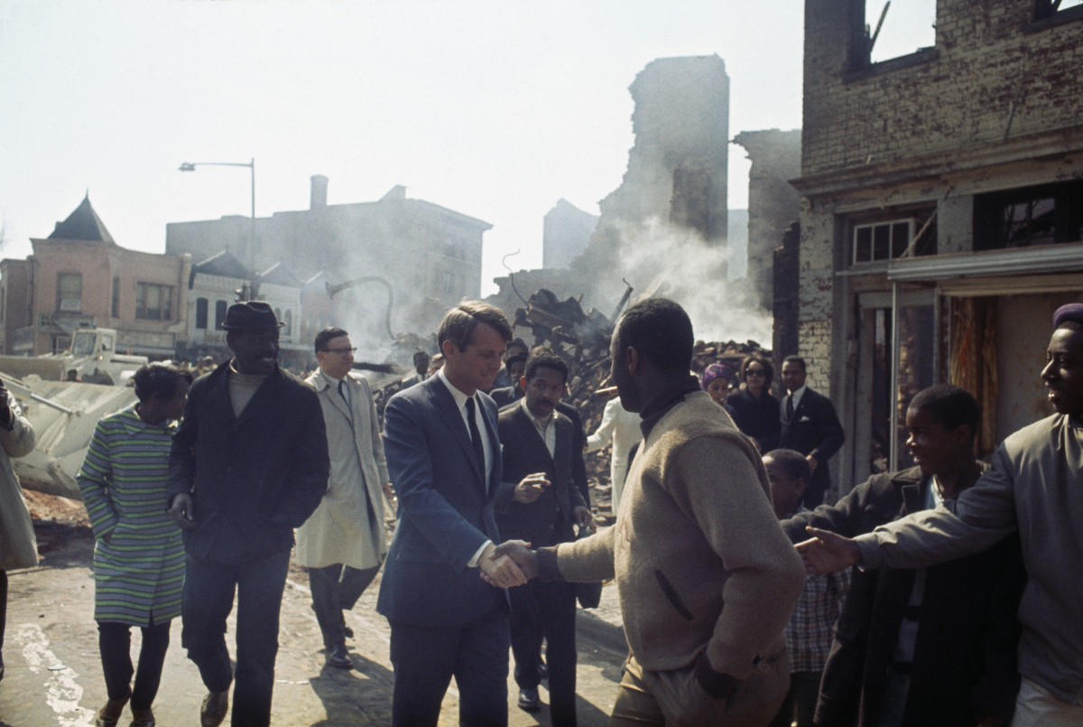 Robert F. Kennedy shaking hands with local residents as he visits damaged properties in Washington, D.C. following the riots and civil disorder triggered by the assassination of Dr. Martin Luther King.