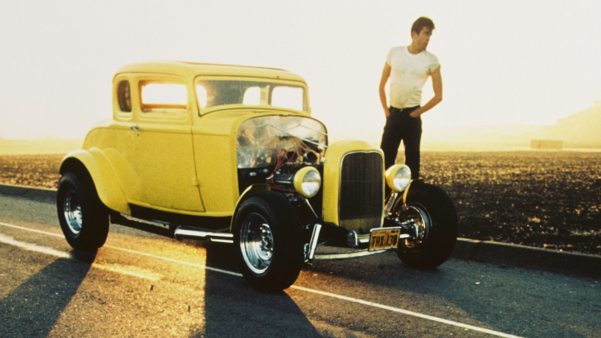 Actor Paul Le Mat, standing beside a Ford Model B five-window coupe, also known as the Deuce Coupe, in a publicity still for the film American Graffiti.