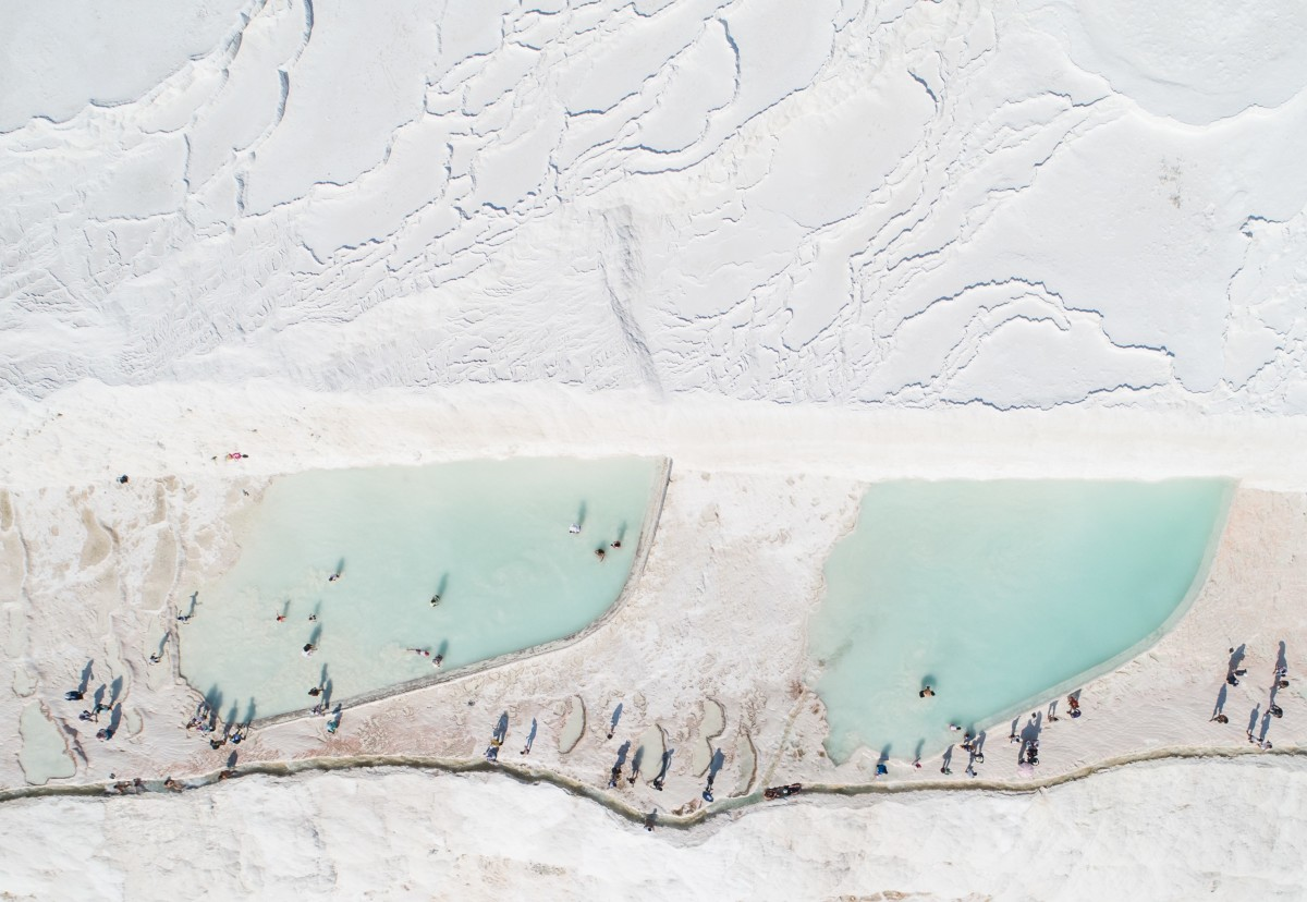 An aerial view of people at the thermal pools of Pamukkale in ancient city of Hierapolis in Denizli, Turkey, 2018. Thermal water have been running at Pamukkale for 2500 years.