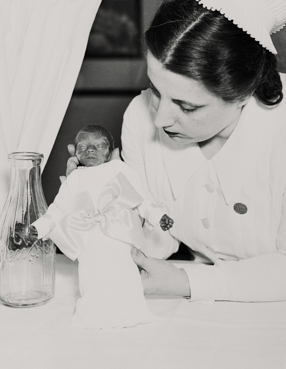 The smallest resident of the baby incubator at Coney Island in 1937 is this baby girl, weighing just 23 ounces, shown with nurse Hildegarde Couney.