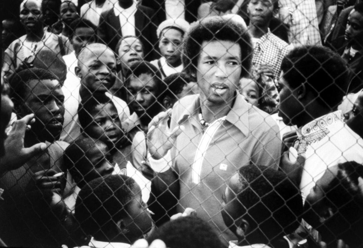 Arthur Ashe surrounded by black youths while visiting Soweto, South Africa.