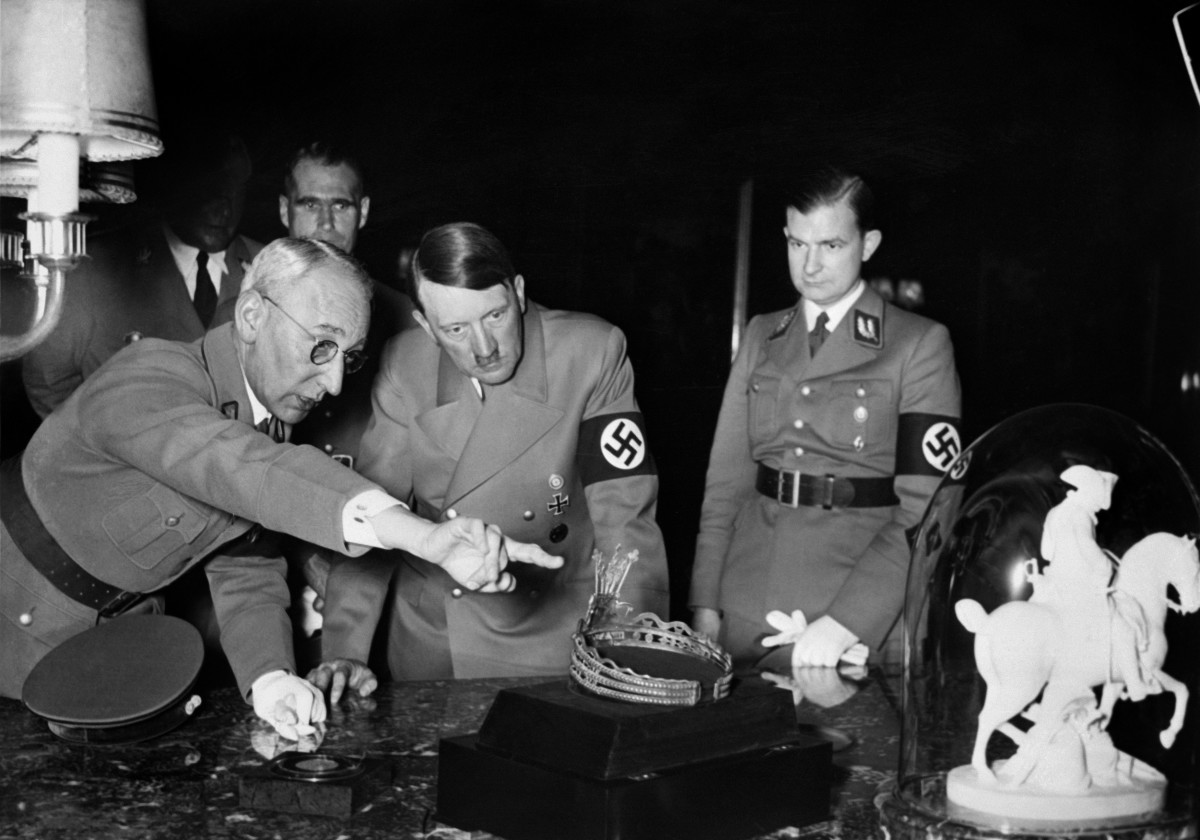 Adolf Hitler is shown looking at a tiara and a sculpture of Napoleon Bonaparte during his visit of an art exhibition. Rudolf Hess stands in the background.