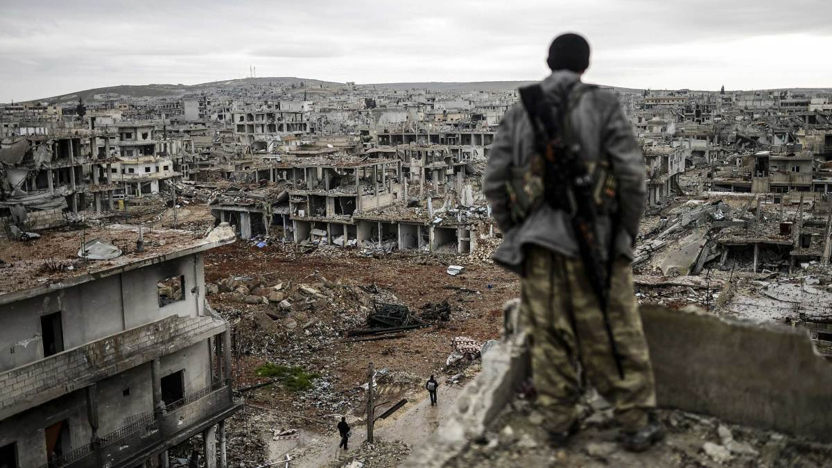 A man stands atop a building looking at the destroyed Syrian town of Kobane, also known as Ain al-Arab, 2015.