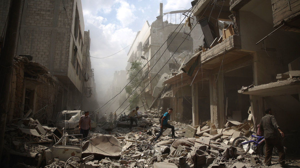 Syrians walk amid the rubble of destroyed buildings following air strikes by regime forces in the rebel-held area of Douma on August 30, 2015.