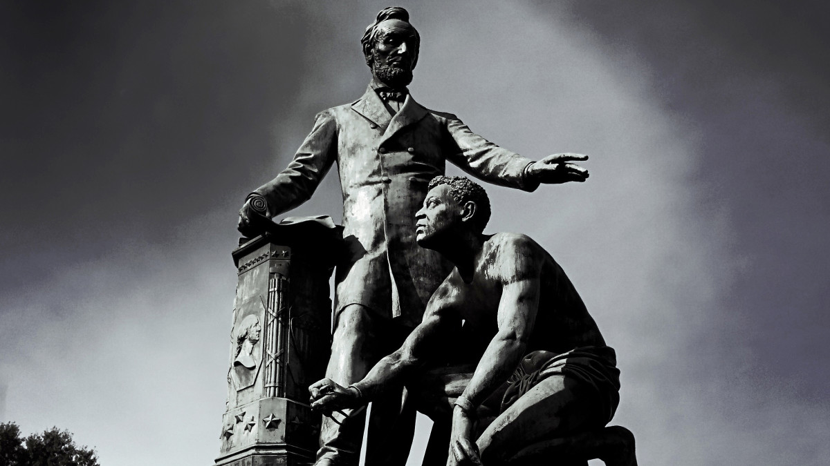 "A statue of President Lincoln in the middle of Lincoln Park in Washington, D.C. The statue depicts Lincoln in his role of the ""Great Emancipator"" freeing a male slave."