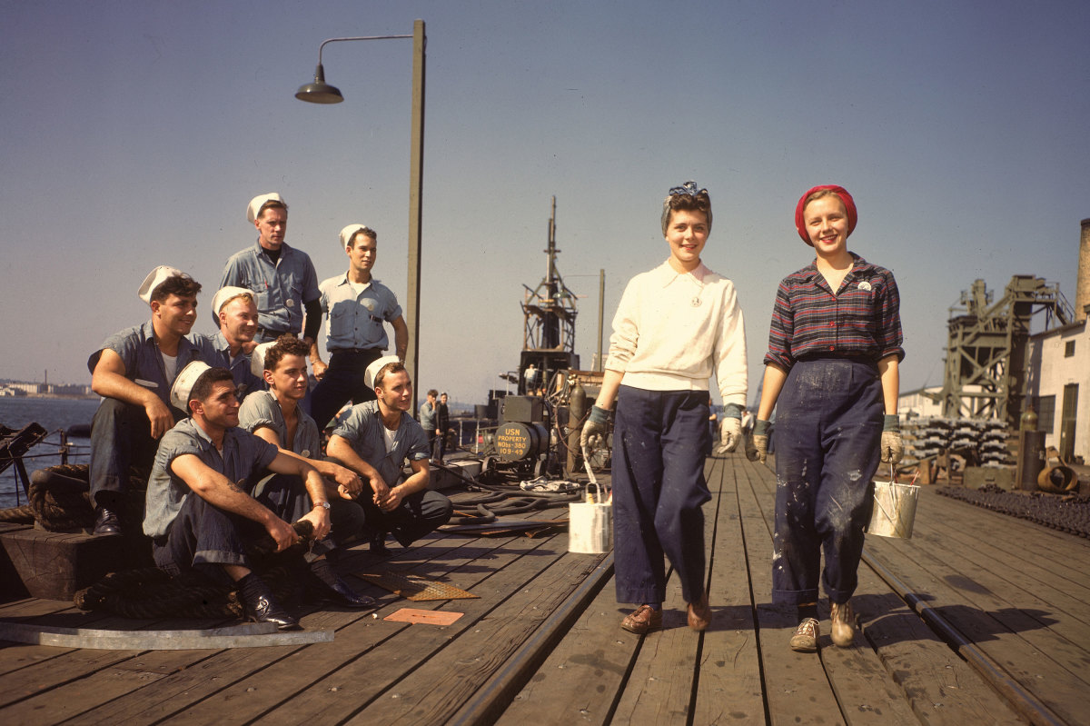Two female war workers walk along a dock at the Electric Boat Company in Groton, Connecticut, 1943. The company produced more than 70 submarines and almost 400 PT boats during World War II.