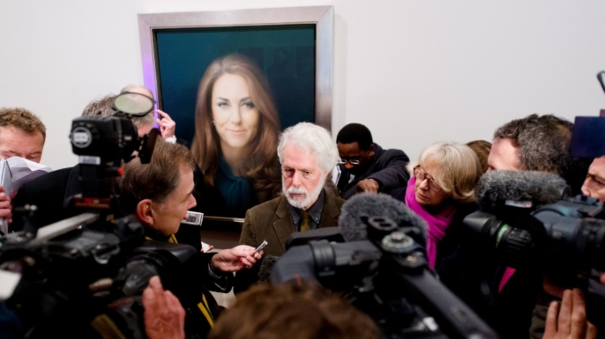 British artist Paul Emsley poses in front of his portrait of Catherine, The Duchess of Cambridge.