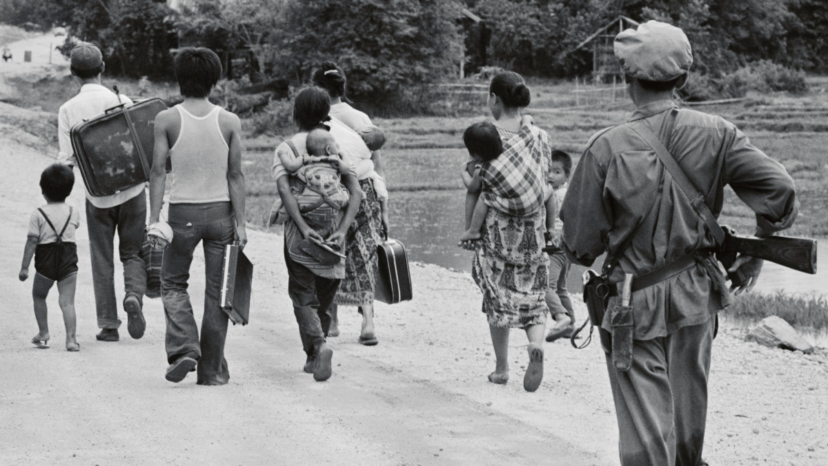 A communist Lao trooper orders citizens to return to their homes following an attempted protest march to the Laotian capital in 1975.
