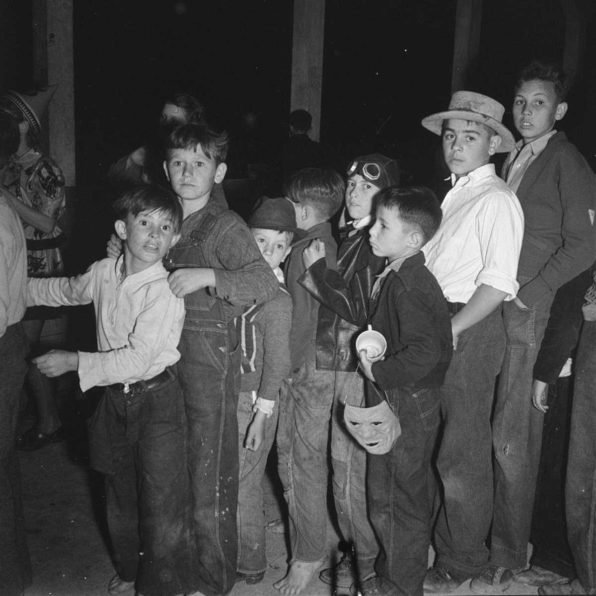 A crowd of boys pushing through a crowd at a Halloween party in the 1930s.