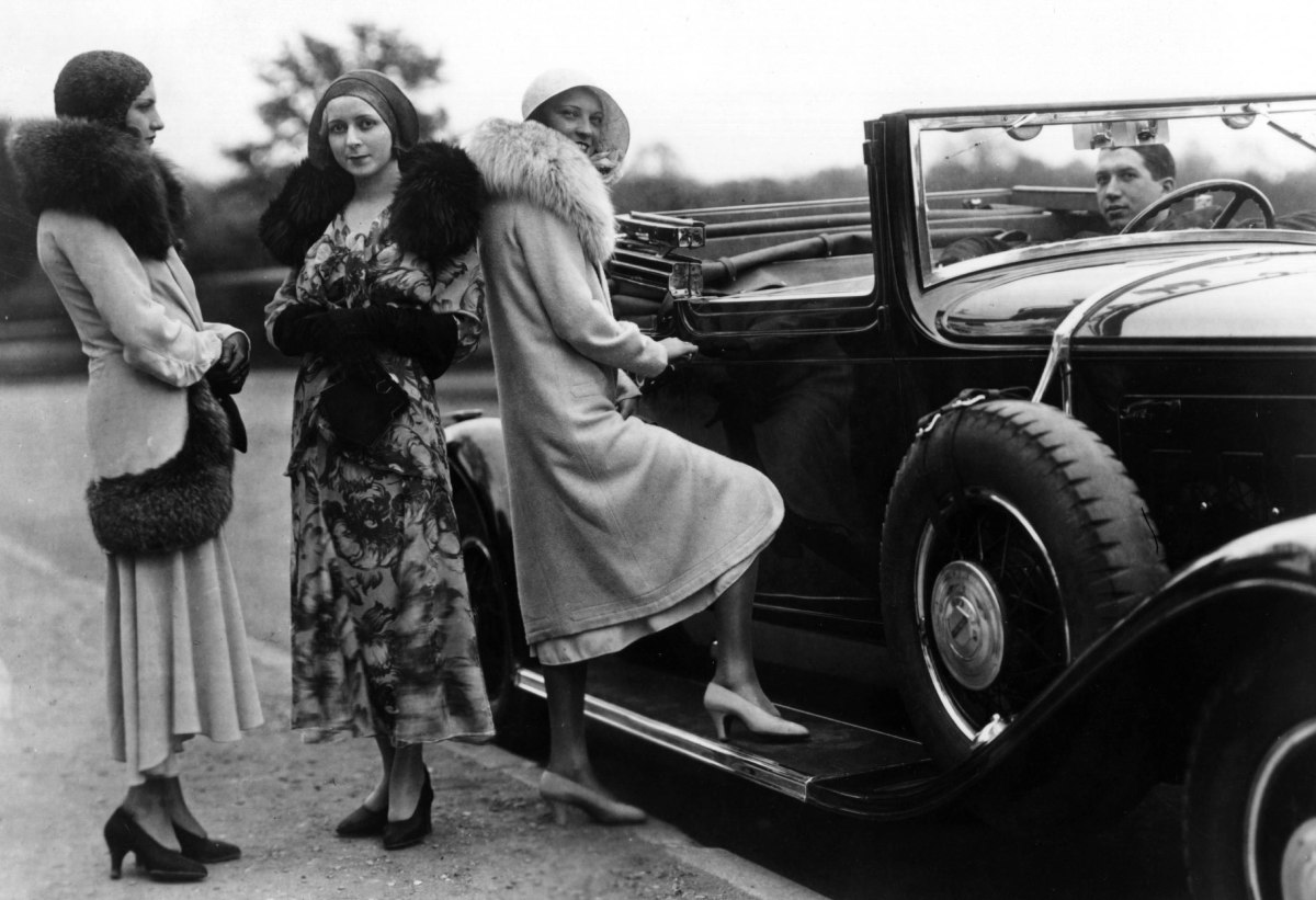 Women in fur coats standing by a luxurious convertible, circa 1920.