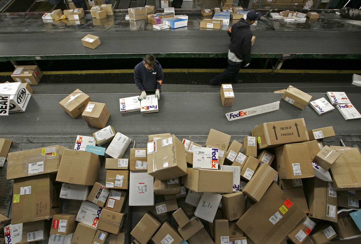 A FedEx worker sorting packages in Oakland, California, 2005. FedEx and UPS began to see an increase of packages as the holiday shipping season gets underway with a high level of online shopping.