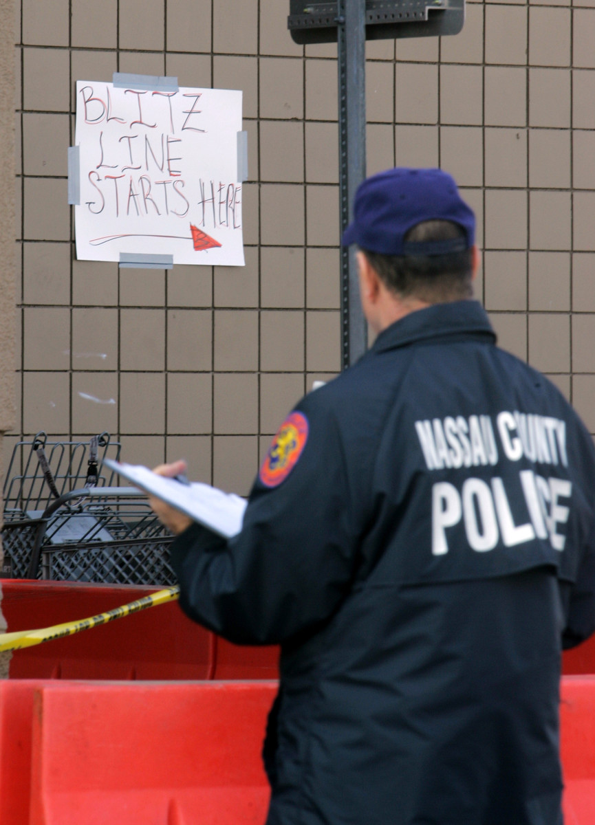 A Nassau County Police Officer looking at a handwritten sign in front of the Wal-Mart in Valley Stream, N.Y. where Jdimytai Damour, a temporary Wal-Mart worker, died after a throng of unruly shoppers broke down the doors and trampled him moments after the Long Island store opened for day-after-Thanksgiving bargain hunting.