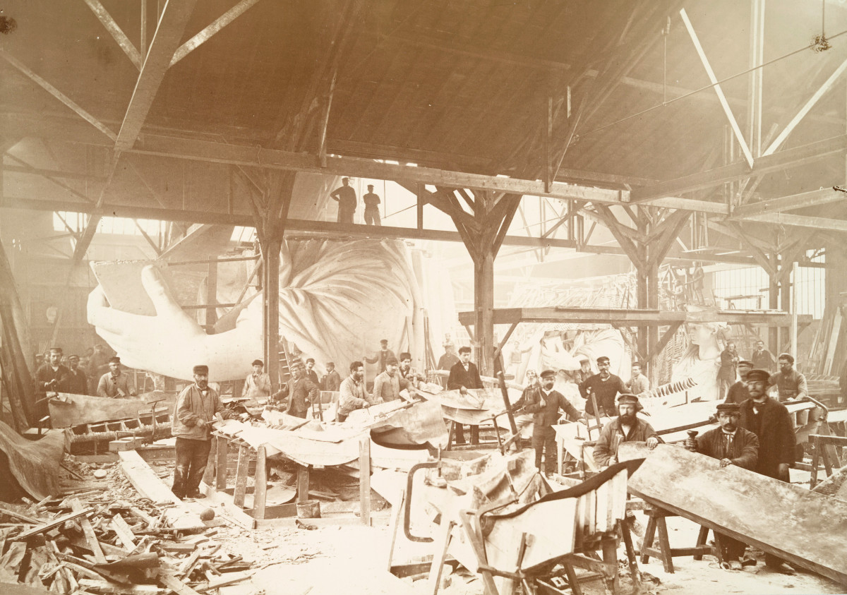 Men in a workshop hammering sheets of copper for the construction of the Statue of Liberty, circa 1883.