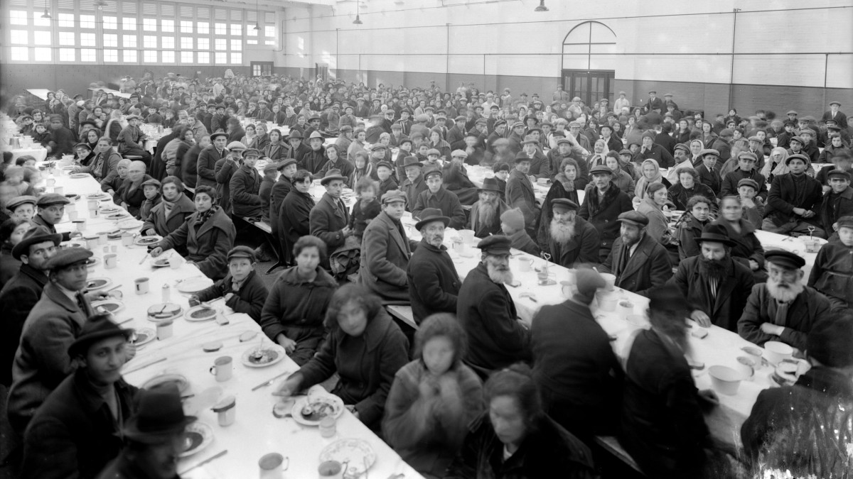 A large group of Jewish immigrants sitting down to dinner in a converted hangar at Atlantic Park, Southampton serving as a hostel for immigrants en route to the U.S. from eastern Europe.