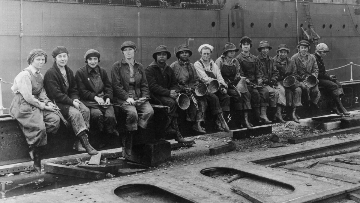 Women rivet heaters and passers on ship construction work in the Navy Yard in Seattle, Washington.